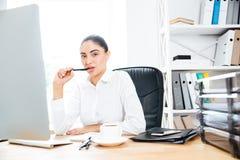 Atrakcyjny powabny bizneswomanu obsiadanie przy jej miejsca pracy mienia piórem zdjęcia stock