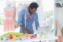 Atrakcyjny projektant mody pracuje na laptopie zdjęcie royalty free