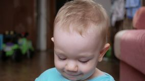 Atrakcyjny 2 roczniak chłopiec spojrzenia przy zmiana wyrazami twarzy, kamerą i uśmiechami i Domowi meblowania błękitny koszula t zbiory