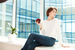 Atrakcyjny rozważny młodej kobiety obsiadanie na nadokiennym parapecie w biurze zdjęcia stock