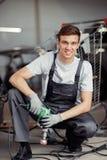 Atrakcyjny samochodowy mechanik w mundurze przy końcówką jego dzień roboczy obraz stock