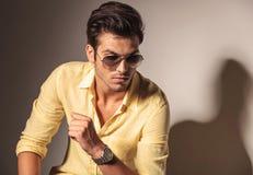 Atrakcyjny seksowny mężczyzna jest ubranym okulary przeciwsłonecznych i żółtą koszula obraz stock