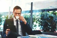 Atrakcyjny seksowny mężczyzna w szkieł pić herbaciany i wyszukiwać wiadomość Zdjęcie Stock