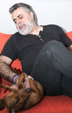 Atrakcyjny senior z białą brodą Bawić się z jamnika psem Obraz Stock