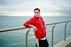 Atrakcyjny sporty biegacz w czerwonych sporta hoodie stojakach na molu opiera na spojrzeniu i poręczu daleko od Zdjęcia Stock
