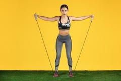 Atrakcyjny sporty młoda kobieta trening z rozciągliwością skrzyknie na zielonej trawie nad żółtym tłem zdjęcie royalty free