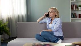 Atrakcyjny starszy kobiety obsiadanie na leżance i dzwonić córce, komunikacja obraz stock