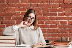 Atrakcyjny studencki dziewczyny gryzienia pióro przy biblioteką Obrazy Royalty Free