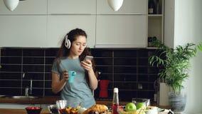 Atrakcyjny szczęśliwy dziewczyna taniec w kuchni podczas gdy wyszukujący ogólnospołecznych środki na smartphone i słuchanie muzyk zdjęcie wideo