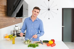 Atrakcyjny szczęśliwy mężczyzna robi jarskiej sałatki na kuchni fotografia royalty free