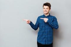 Atrakcyjny szczęśliwy młody człowiek stoi nad popielatą ścianą i wskazywać obraz royalty free