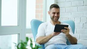 Atrakcyjny uśmiechnięty mężczyzna używa cyfrowego pastylki obsiadanie w krześle przy balkonem w loft nowożytnym mieszkaniu Zdjęcie Stock