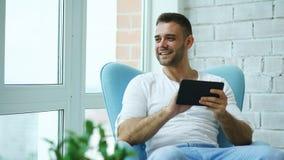 Atrakcyjny uśmiechnięty mężczyzna używa cyfrowego pastylki obsiadanie w krześle przy balkonem w loft nowożytnym mieszkaniu Obraz Stock