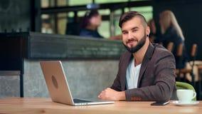 Atrakcyjny uśmiechnięty męski biznesmen pozuje siedzieć na stołowym pracującym używa laptopie przy kawiarnią zbiory wideo