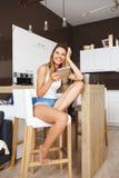 Atrakcyjny uśmiechnięty młodej dziewczyny obsiadanie przy kuchnią i słucha muzyka przyglądając się na bok fotografia royalty free
