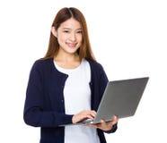 Atrakcyjny uśmiechnięty młodej kobiety mienia laptop fotografia stock