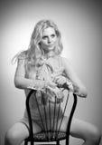 Atrakcyjny uczciwy włosy model w z elegancką nagą bluzką siedzi provocatively na krześle, studio strzał portret mody Obraz Royalty Free