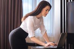 Atrakcyjny ufny bizneswoman opiera nad laptopem Zdjęcia Stock