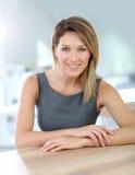 Atrakcyjny uśmiechnięty bizneswoman przy biurem Fotografia Royalty Free