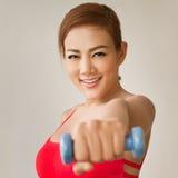 Atrakcyjny, uśmiechnięty kobieta model z dumbbell uderzać pięścią, Obraz Stock