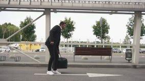 Atrakcyjny właśnie przyjeżdżający lotniskowy brodaty biznesmen patrzeje dla taxi zdjęcie wideo
