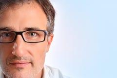 Atrakcyjny w średnim wieku mężczyzna z eyeglasses tła błękitnym detai fotografia royalty free