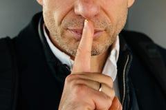 Atrakcyjny zarośnięty dorosły mężczyzna z palcem na wargach robi ciszy obraz royalty free