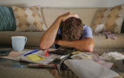 Atrakcyjny zmartwiony zaakcentowany mężczyzna kalkuluje miesiąca podatku koszty z kalkulator księgowości zapłatami robi bank papi Zdjęcie Stock