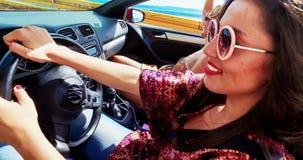 Atrakcyjnych kobiety kręcenia kierownicy napędowych przyjaciół odwracalny samochód, oceniać zdjęcie wideo