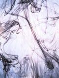 Atramentu zawijas w wodzie na koloru tle Farby pluśnięcie w wodzie Miękki rozpowszechnienie kropelki barwiony atrament wewnątrz Zdjęcie Royalty Free