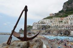 ATRANI, ITALIA, EL 28 DE JUNIO DE 2014: Detalle en el ancla con la playa del atrani detrás La gente es relajante y que toma el so fotografía de archivo