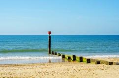 Atraque las virutas en una playa arenosa, un océano azul y una arena amarilla, soleados Foto de archivo