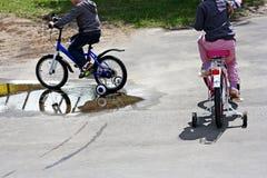 Através das poças em bicicletas Fotografia de Stock Royalty Free