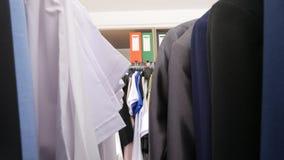 Atravessar ganchos com negócio e roupa ocasional video estoque