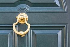 08 09 2018 Atri, Itália - aldrava de porta dourada em uma porta escura tradicional fotografia de stock royalty free