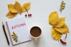 Atributos do outono, do café e do caderno em uma placa branca Foto de Stock Royalty Free