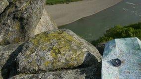 Atributos do turista: mapa e compasso em um fundo rochoso da natureza do rio conceito do curso Imagem de Stock