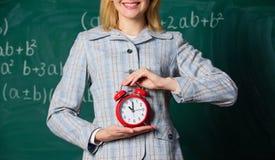 Atributos dos professores Despertador nas mãos do fundo do quadro da sala de aula do professor ou do professor Disciplina da esco fotografia de stock royalty free