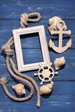 Atributos marinhos Corda, quadro, âncora de madeira e volante em um fundo de madeira azul Fotografia de Stock