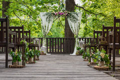 Atributos Wedding Cerimónia de casamento As colunas brancas de um casamento arqueiam, decorado com flores, e os bancos marrons Qu imagens de stock royalty free