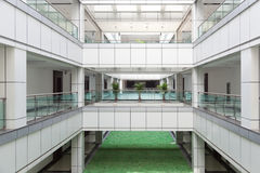 Atrium in an office building. Open atrium with facing corridors and man made lawn floor in an office building stock image