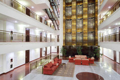 Atrium with red armchairs, couches and elevators. In stylish hotel Stock Photos
