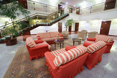 Atrium with red soft armchairs, couches and stairs. In stylish hotel Stock Images