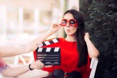 Atriz surpreendida com óculos de sol desproporcionados que grava a cena do filme Imagem de Stock