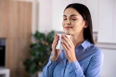 Atrractive使喝她的咖啡的妇女满意 免版税库存照片