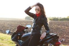 atrractive照片女服时髦树荫,皮夹克,保留在头,在motorrbike附近的姿势的手,享受悠闲时间,有 库存图片