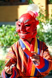 Atsara Joker wearing red traditional Bhutanese dress entertain. Ing people in Mask Dance Festival in Bhutan Stock Images