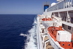 AtSea. Cruise ship underway on the smooth ocean, showing lifeboats Stock Image