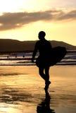 atSunset de la persona que practica surf Foto de archivo libre de regalías