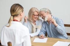 Att älska att bry sig pensionären åldrades par som skrattar undertecknande dokument på M royaltyfri bild